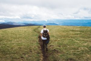 Man hiking across a grassy terrain with clouds in the distance