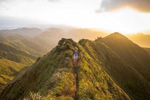 Woman hiking along the top of a grassy mountain with the warm sun low in the sky behind her