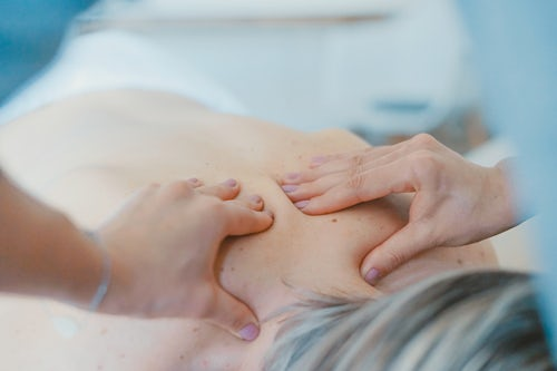 Hands massaging back of a woman at Glasgow spa