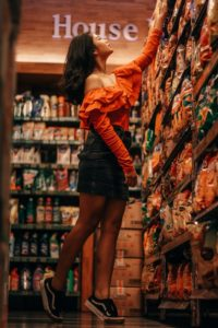 Woman on her tip toes reaching a high shelf while shopping