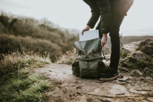 Woman packing her bag as she stands on a hiking trail